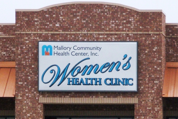MHC Women's Health Clinic - Lighted Cabinet with Painted Embossed Faces Installed on Brick Storefront